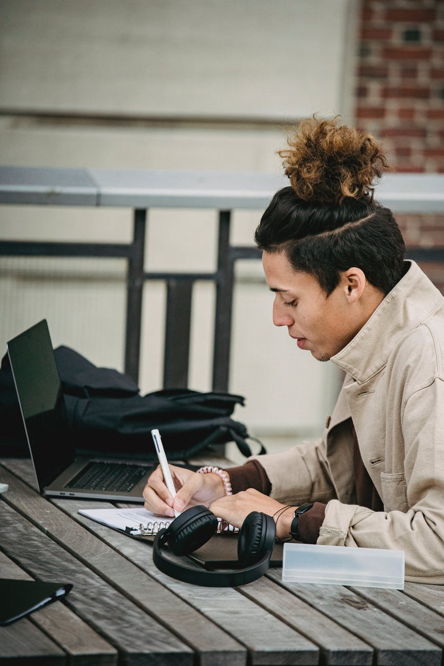 young serious ethnic man with trendy hairstyle writing at table